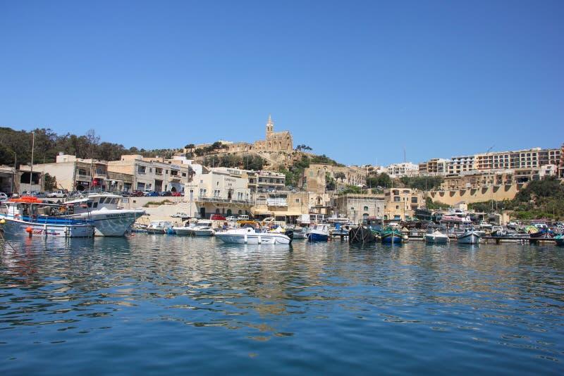 Mgarr, Мальта - май 2018: Взгляд Mgarr паромного терминала Gozo Залив с яхтами на переднем плане и старый город с церковью на вер стоковое изображение