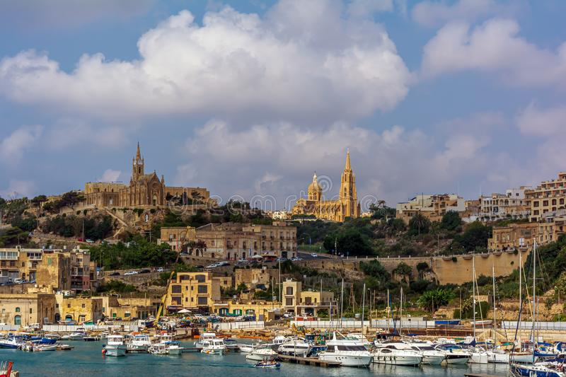 Yachts, boats and ships in Mgarr harbour, at Gozo, Malta, with Lourdes Chapel and Ghajnsielem Parish Church on the hill. royalty free stock photo