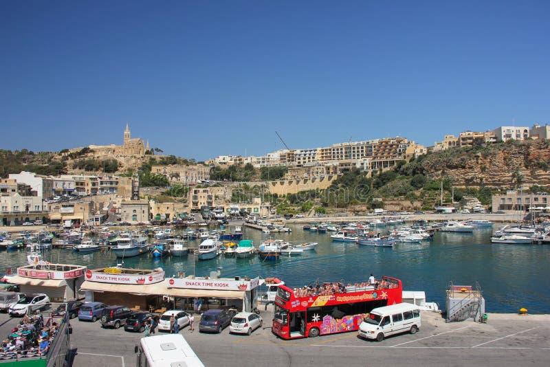 Mgarr Malta - Maj 2018: Sikt Mgarr för Gozo färjaterminal med den touristic bussen, mellanmålstänger, yachter och kyrkan på bakgr royaltyfria bilder