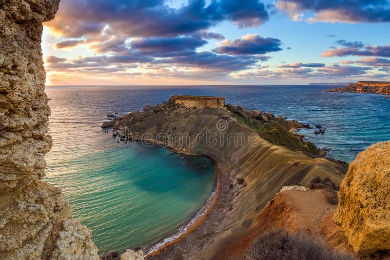 Mgarr Malta - panorama av Gnejna och Ghajn Tuffieha skäller, den mest härliga stranden två i Malta på solnedgången arkivfoto