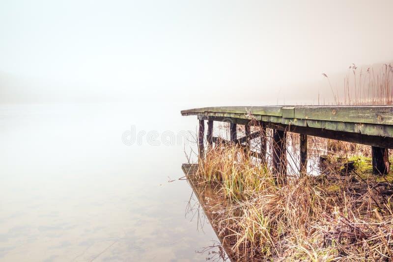 Mglisty jezioro po środku starego drewnianego mostu i lasu zdjęcie royalty free