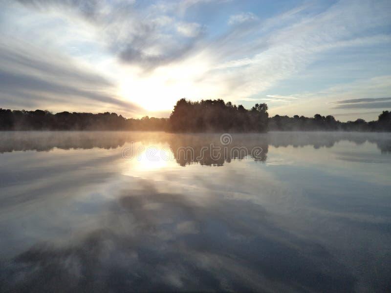 Mglisty wschód słońca nad małym jeziorem obrazy stock