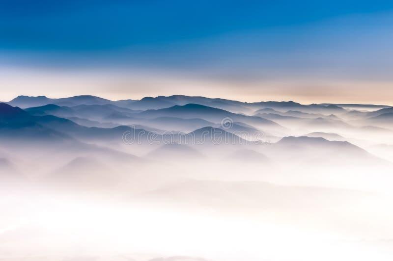 Mglistych gór krajobrazowy widok z niebieskim niebem obraz stock