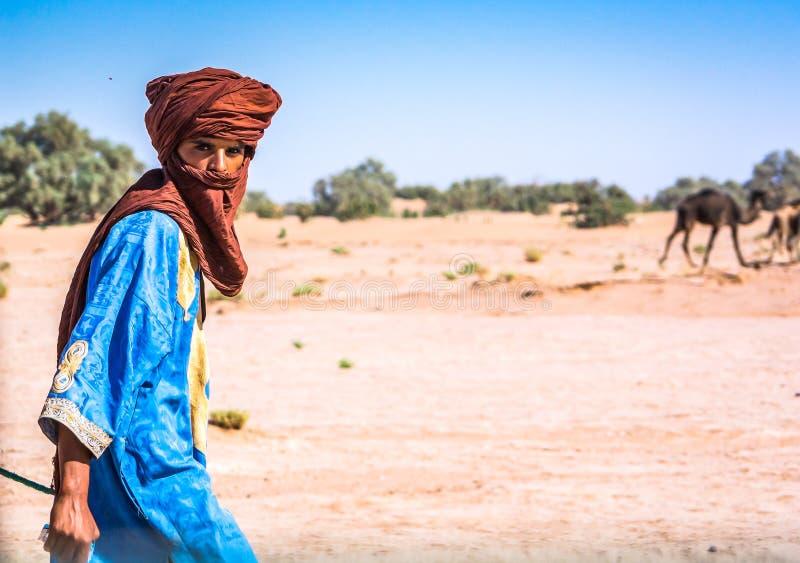 MHamid, Marrocos - 10 de outubro de 2013 Berber novo que anda no deserto Sahara na roupa tradicional com camelos carregados foto de stock