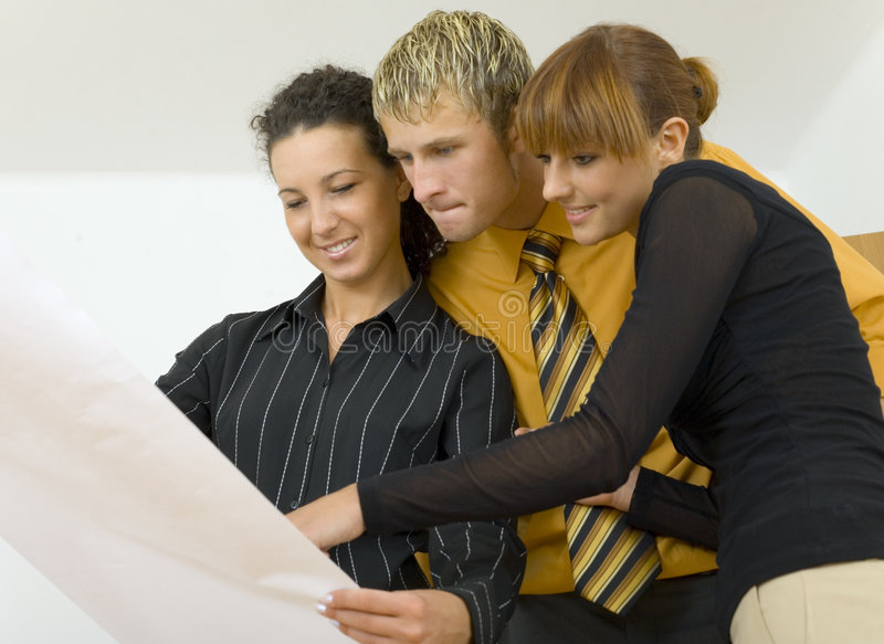 Mhm...ok... Three people standing in front of piece of paper. Two womans are smiling, man is thinking about something. Gray background stock image
