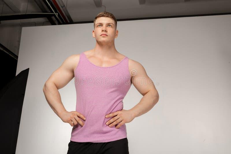 Mięśniowy młody człowiek w różowej koszulce pozuje z rękami na pasku fotografia stock