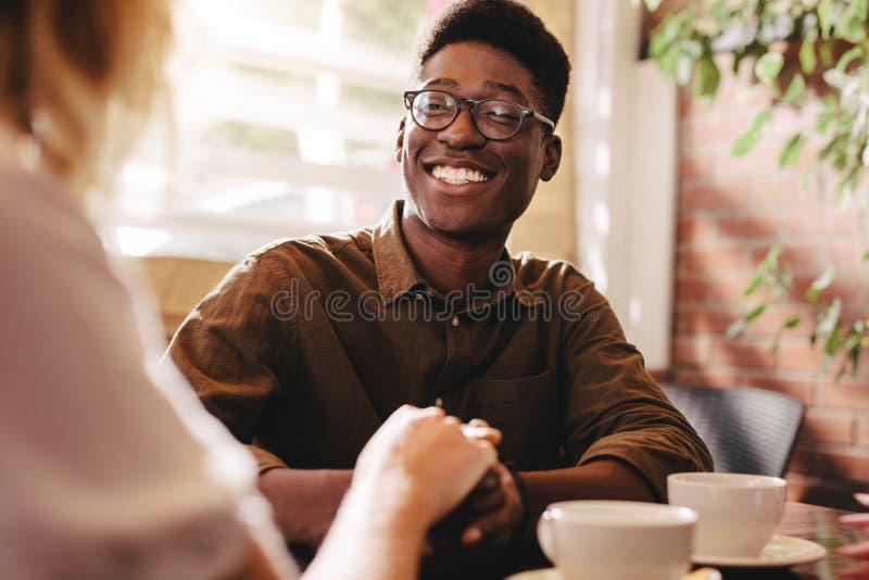Międzyrasowa para na dacie przy kawiarnią zdjęcie stock