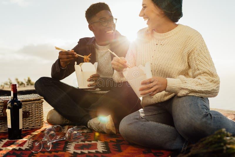 Międzyrasowa para na pinkinie cieszy się mieć jedzenie zdjęcia royalty free