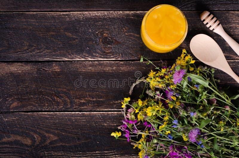 Miód, dzicy kwiaty i łyżka na drewnianym tle, Uwalnia przestrzeń dla twój teksta obrazy stock