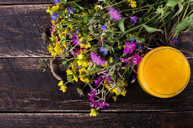 Miód, dzicy kwiaty i łyżka na drewnianym tle, Uwalnia przestrzeń dla twój teksta obrazy royalty free
