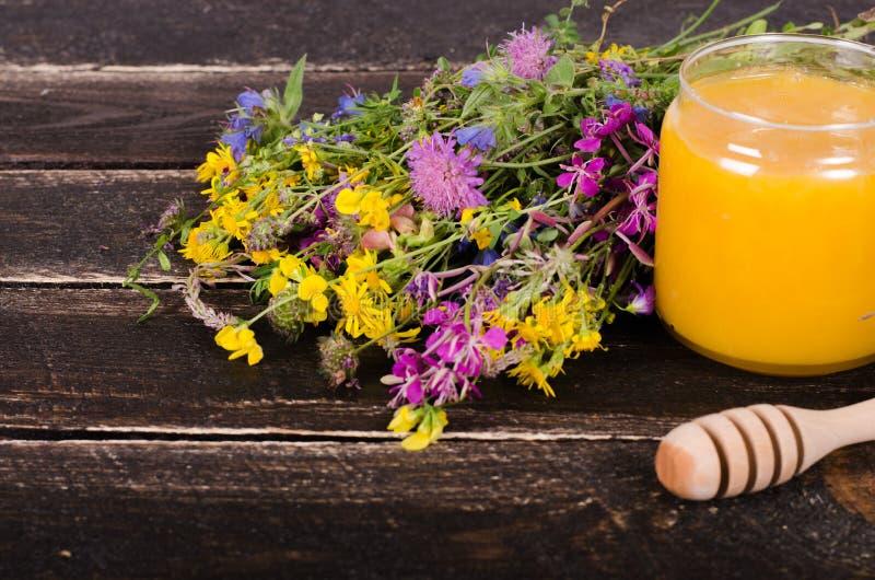 Miód, dzicy kwiaty i łyżka na drewnianym tle, Uwalnia przestrzeń dla twój teksta fotografia stock