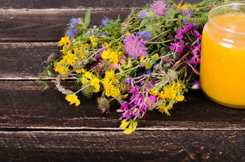 Miód, dzicy kwiaty i łyżka na drewnianym tle, Uwalnia przestrzeń dla twój teksta fotografia royalty free