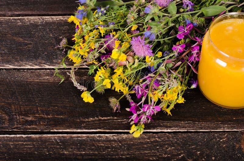Miód, dzicy kwiaty i łyżka na drewnianym tle, Uwalnia przestrzeń dla twój teksta zdjęcia royalty free