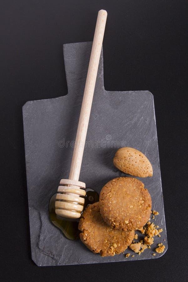 Miód i ciastka na kartonowym iłołupku na Czarnym tle fotografia royalty free