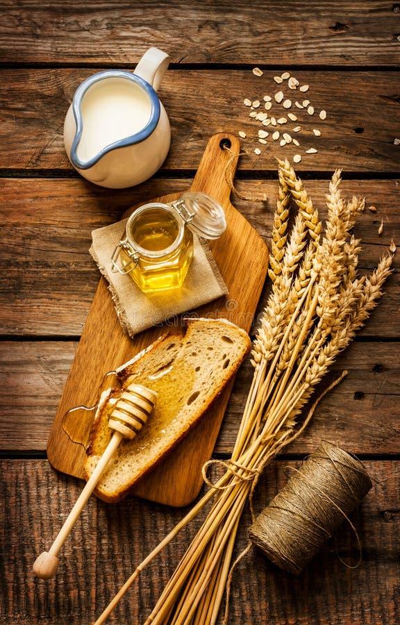 Miód w słoju, plasterek chleb, banatka i mleko na rocznika drewnie, zdjęcia royalty free