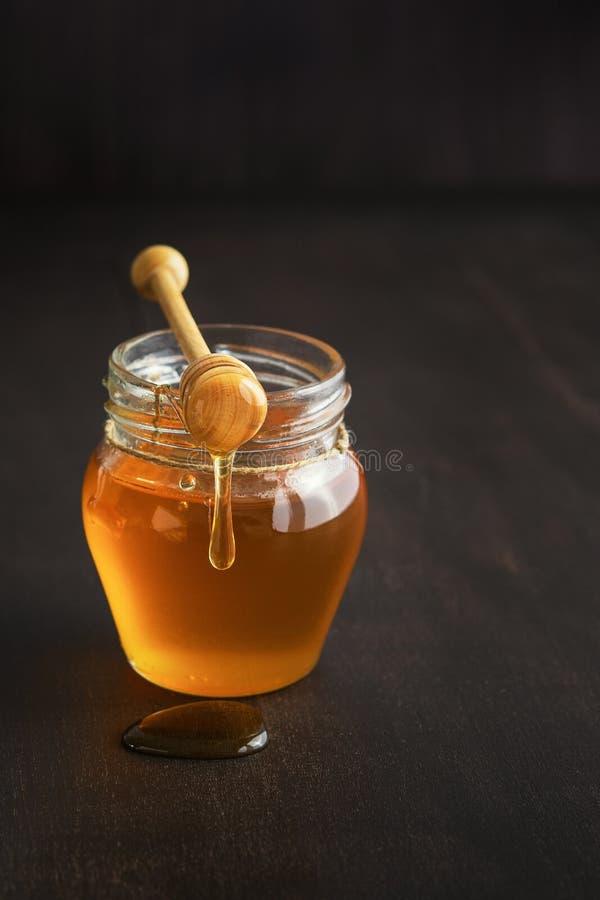 Miód w szklanym słoju z miodową chochlą na nieociosanym drewnianym stołowym tle fotografia royalty free