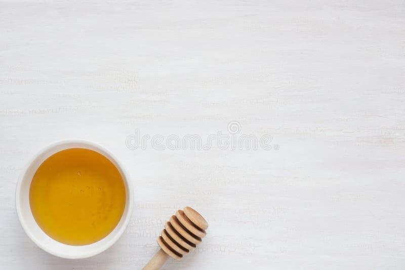 Miód w talerzu i miodowym kiju na lekkim tle Odbitkowa przestrzeń dla teksta obrazy royalty free