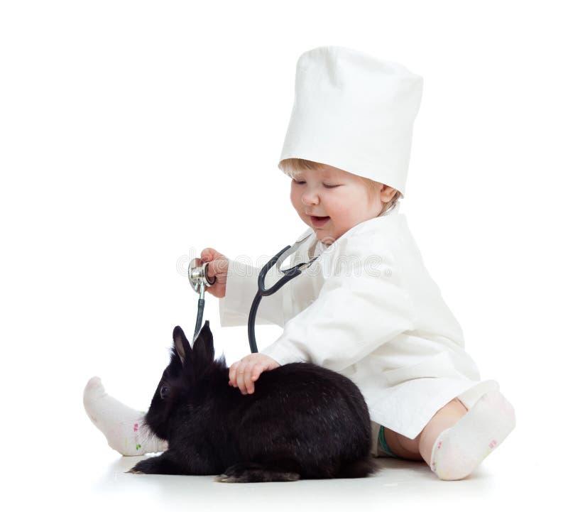 Miúdo adorável com roupa do coelho do doutor e do animal de estimação imagem de stock