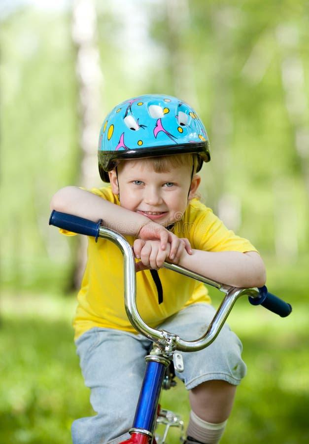 Miúdo agradável weared no capacete na bicicleta fotos de stock royalty free
