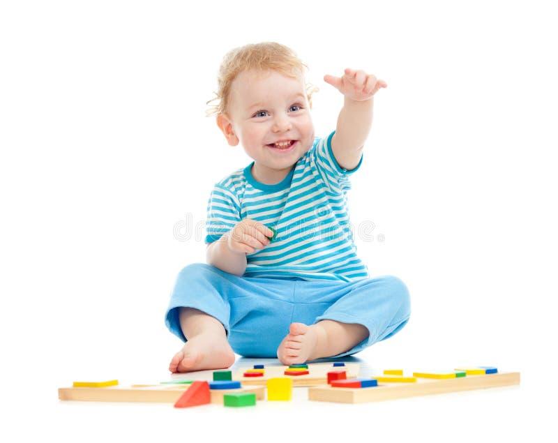 Miúdo alegre feliz que joga brinquedos educacionais imagens de stock