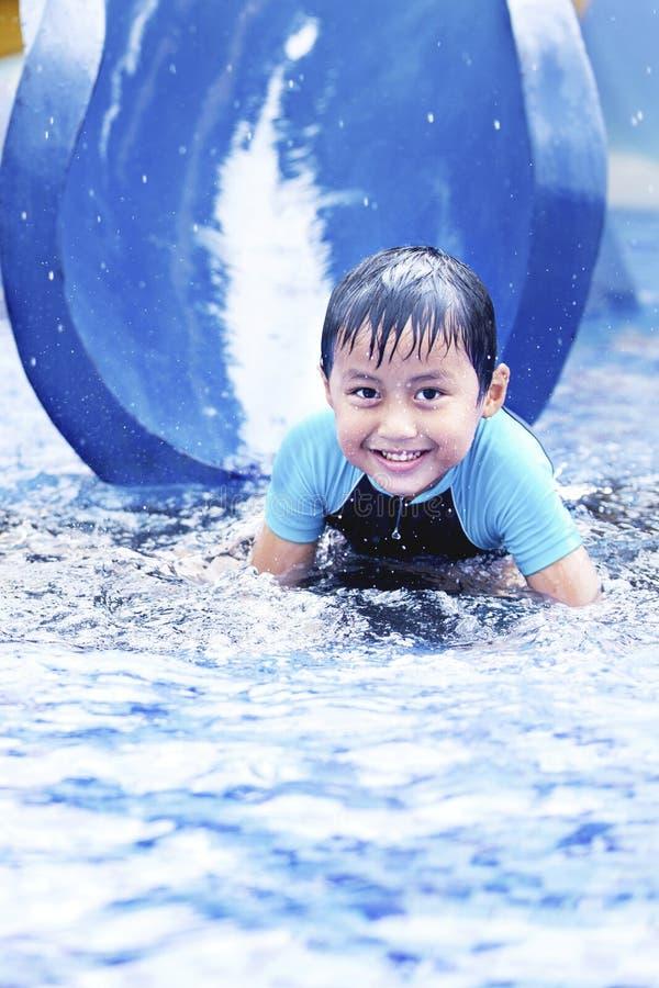 Miúdo asiático feliz na corrediça de água imagem de stock