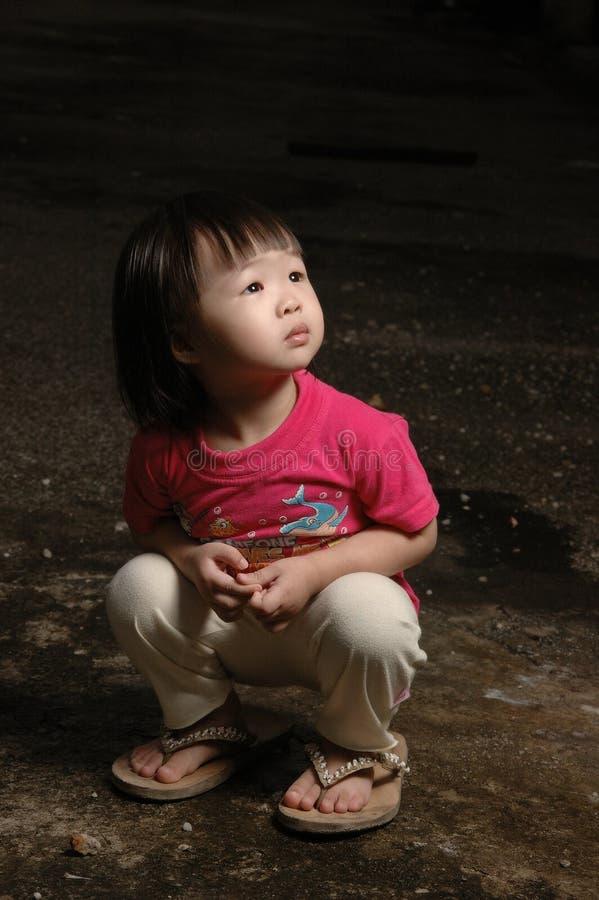 Miúdo asiático na obscuridade imagens de stock royalty free