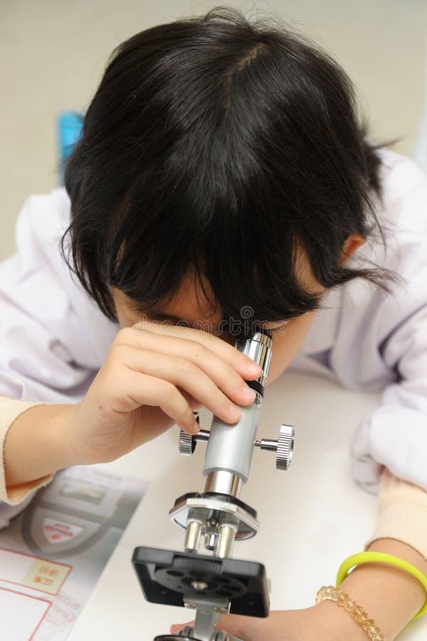 Miúdo Asiático Que Olha No Microscópio Fotos de Stock Royalty Free
