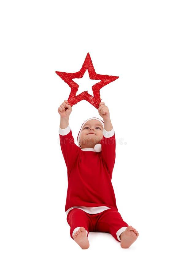 Miúdo bonito no traje de Santa com estrela grande imagem de stock