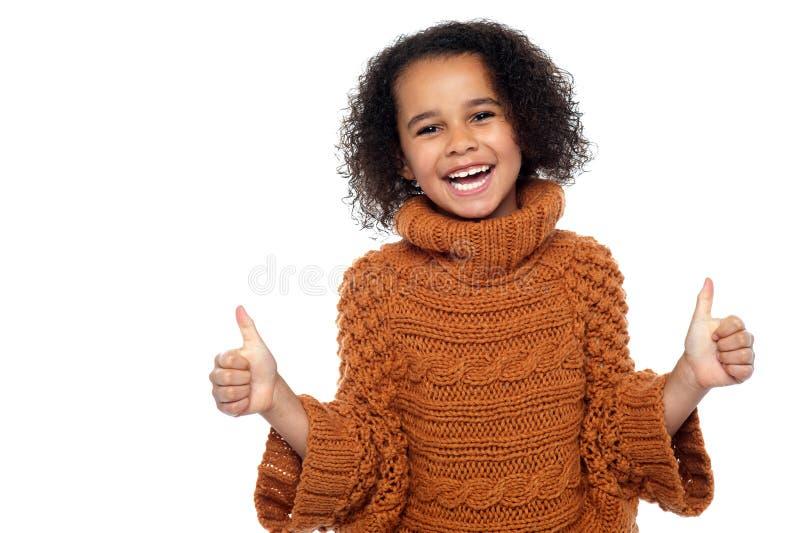 Miúdo bonito que ri e que mostra os polegares dobro acima imagens de stock royalty free