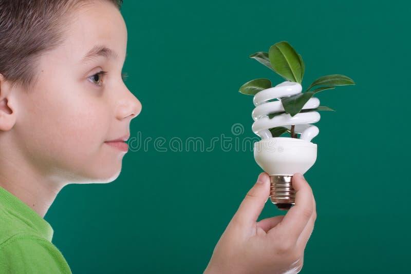 Miúdo com bulbo da economia de energia imagem de stock