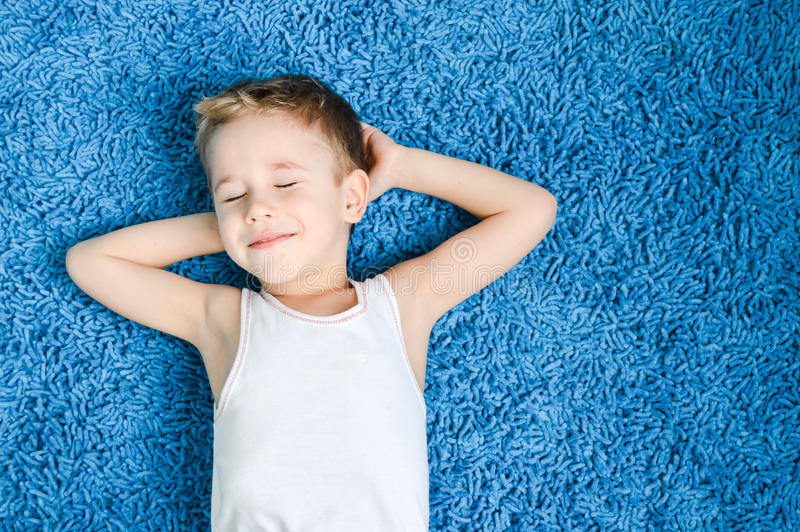 Miúdo feliz no assoalho na sala de visitas em casa com os olhos fechados fotos de stock