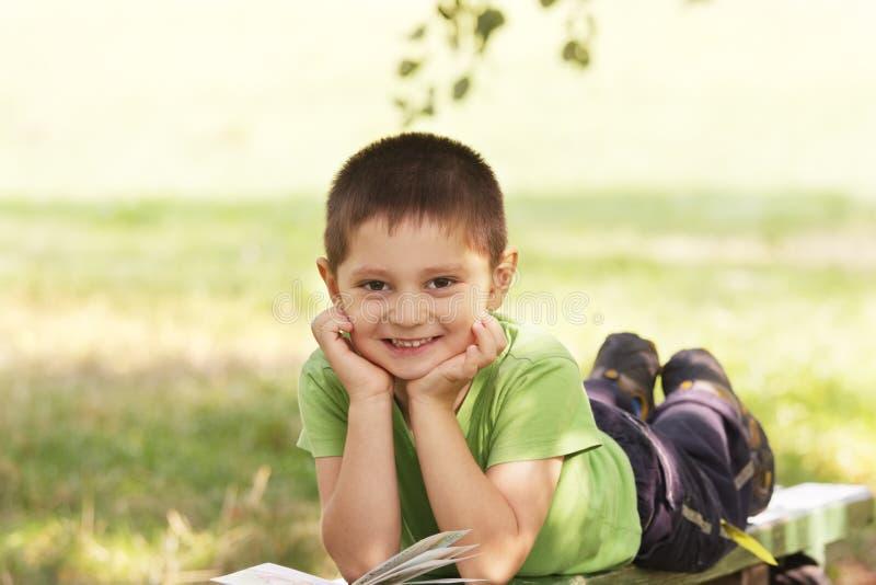 Miúdo de sorriso pequeno com o livro no parque fotos de stock royalty free