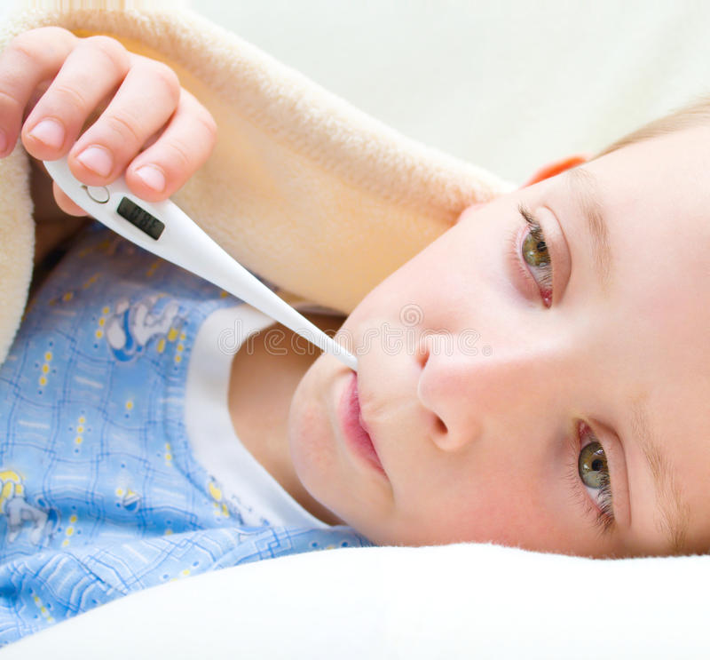 Miúdo doente e triste na cama imagem de stock