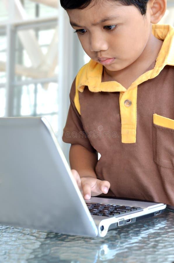 Miúdo esperto que usa o computador portátil fotos de stock royalty free
