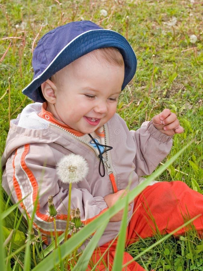 Miúdo feliz no prado do dente-de-leão fotografia de stock