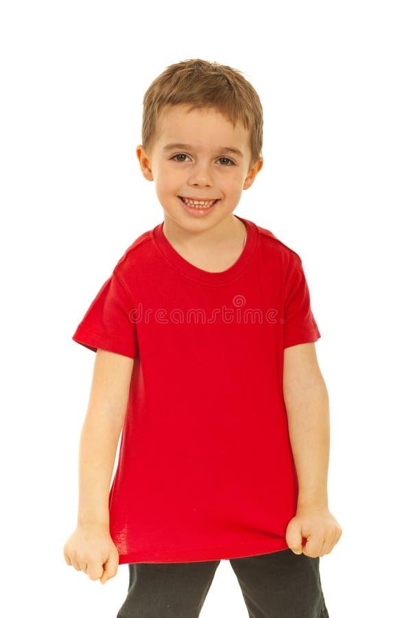 Miúdo feliz que mostra seu t-shirt vermelho em branco imagens de stock royalty free
