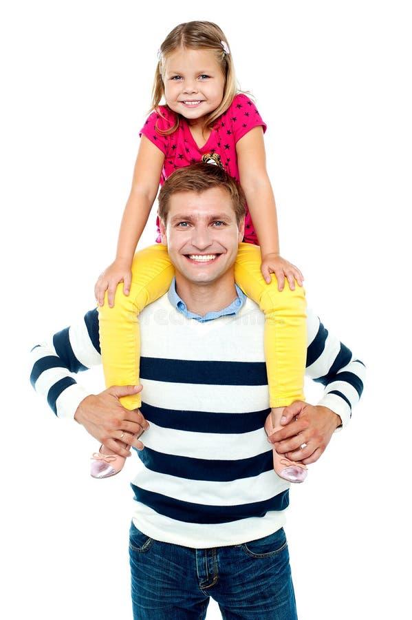 Miúdo loving do divertimento que senta-se em ombros do seu pai imagem de stock royalty free