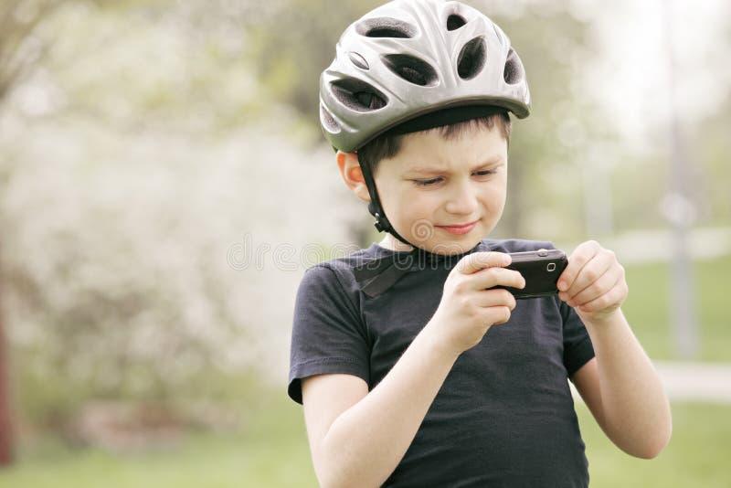 Miúdo no capacete que olha a câmera do telefone imagens de stock