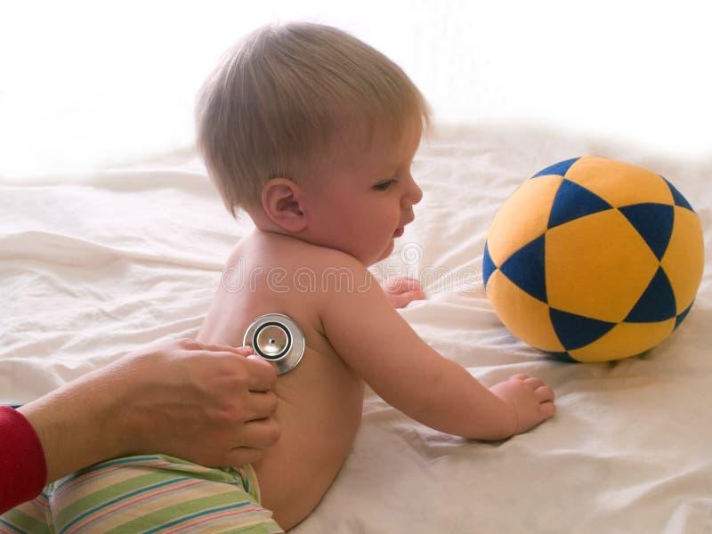 Miúdo paciente de escuta do doutor com estetoscópio imagens de stock royalty free