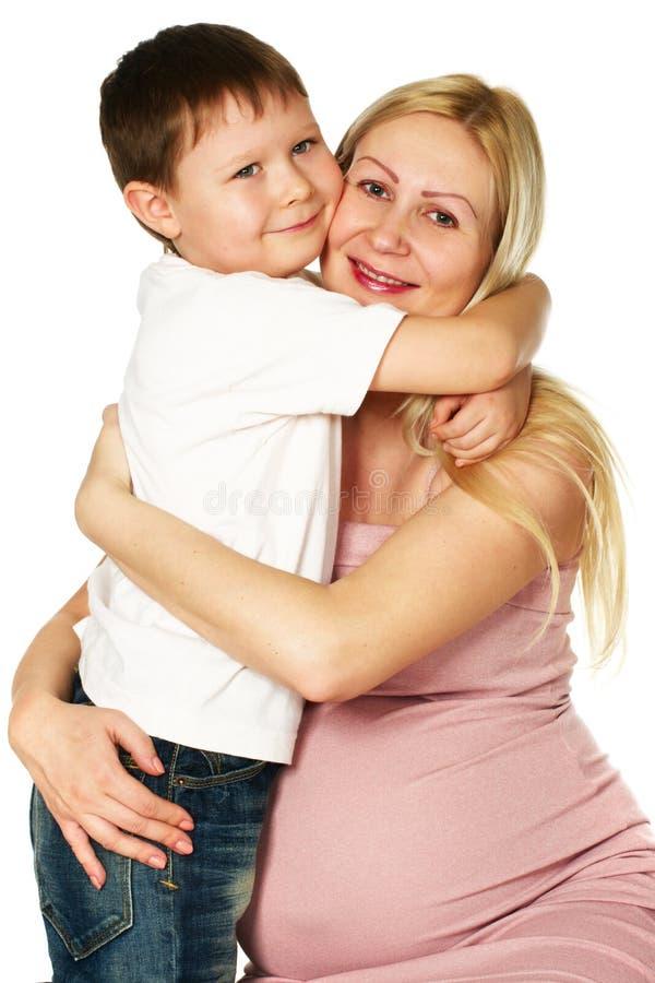 Miúdo que abraça sua matriz grávida foto de stock