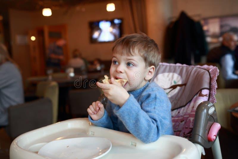 Miúdo que come a pizza imagem de stock royalty free