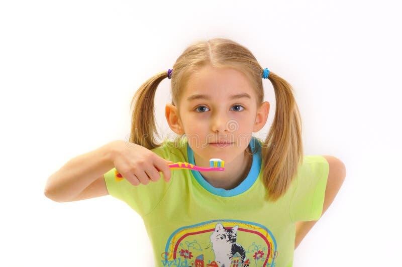 Miúdo que escova seus dentes isolados no branco fotografia de stock