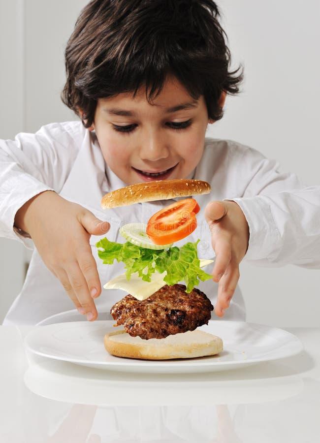 Miúdo que faz o hamburguer imagens de stock royalty free