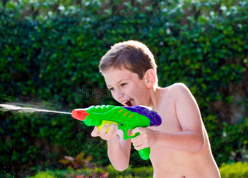 Miúdo que joga com brinquedos da água foto de stock royalty free