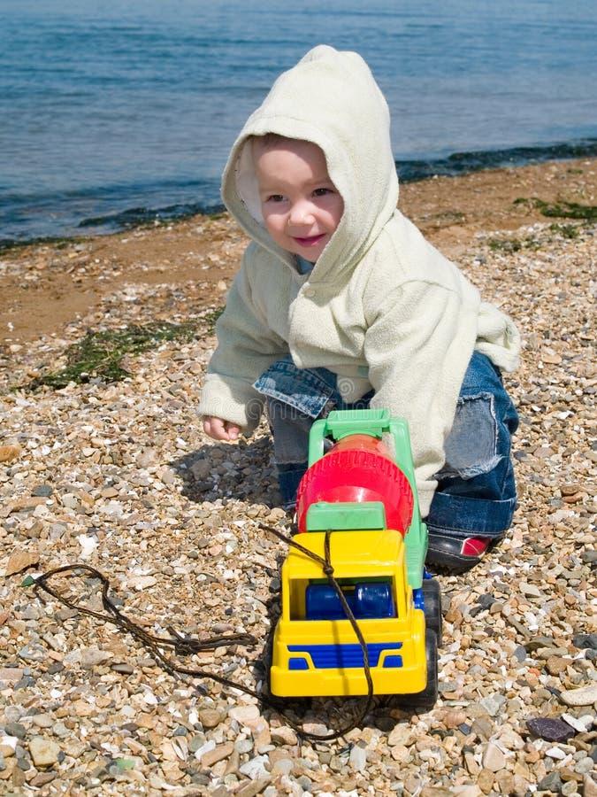 Miúdo que joga com o carro na praia fotografia de stock