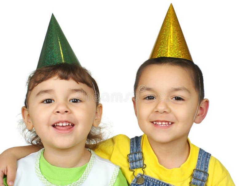 Miúdos com chapéus do partido fotografia de stock