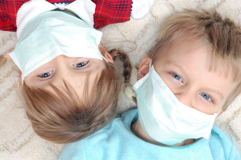 Miúdos com máscaras protetoras do madicine fotografia de stock royalty free