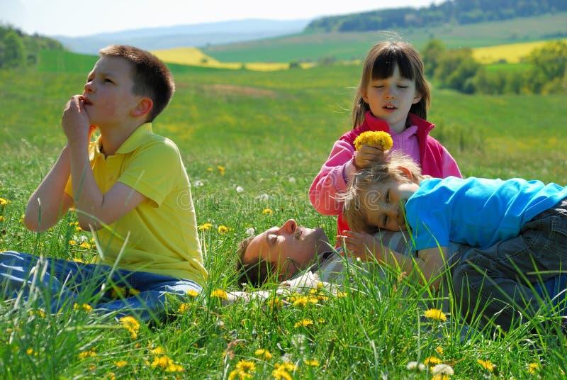 Miúdos com o paizinho no prado imagens de stock royalty free
