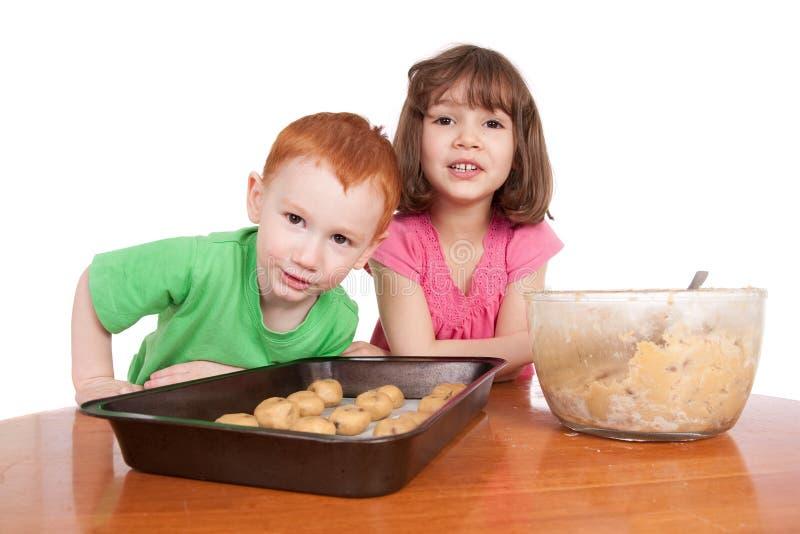 Miúdos com os cookes da microplaqueta de chocolate a cozer fotos de stock royalty free