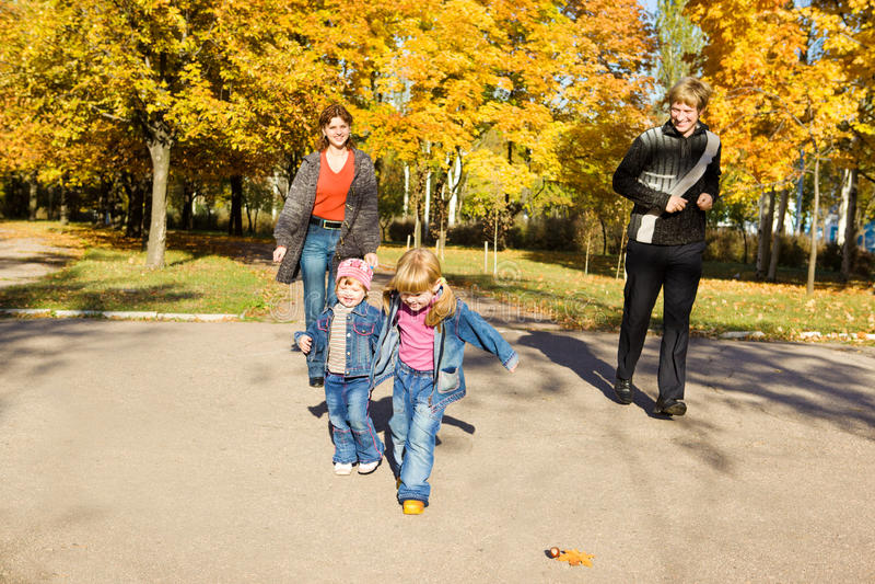 Miúdos com pais no parque do outono imagens de stock